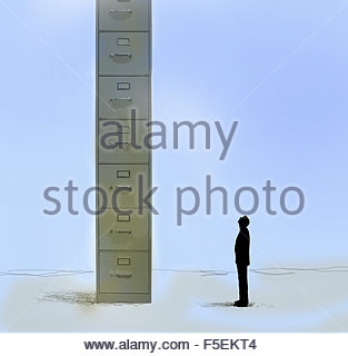 Businessman looking up at huge filing cabinet - Stock Photo