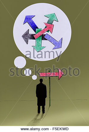 Confused businessman at signpost thinking about arrows pointing in different directions - Stock Photo