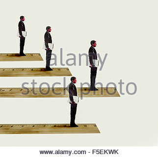 Businessmen standing in rank order on rulers - Stock Photo