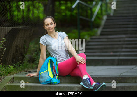 Young athlete girl sitting on the stone stairs in the Park. - Stock Photo
