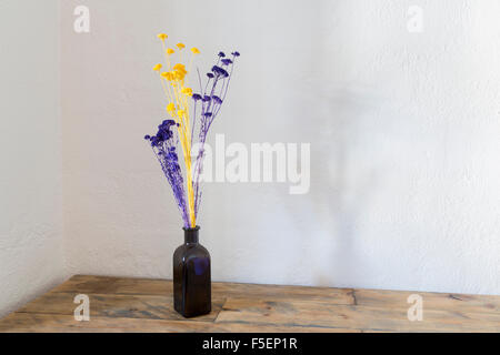 Purple and yellow dried flowers in blue bottle vase on an old wooden table - Stock Photo