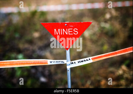 Triangular, red 'mines' sign on taped off mine field - Stock Photo