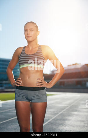 Female runner standing with her hands on hips looking away. Determined woman athlete on race track in athletics - Stock Photo