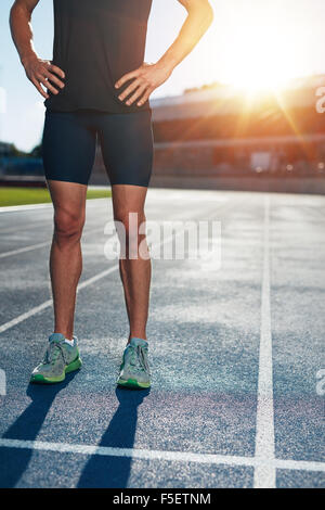 Low section shot of athlete man standing on race track with his hands on hips. Cropped shot of male runner on athletics - Stock Photo
