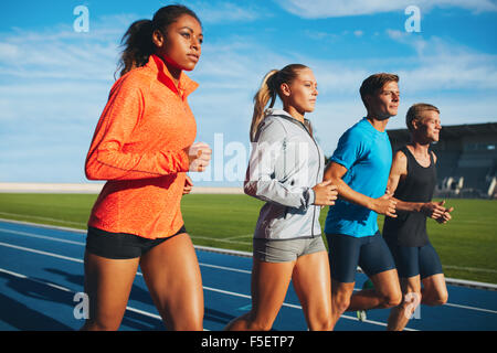 Group of diverse sports person practicing running in stadium. Male and female athletes running together on racetrack. - Stock Photo