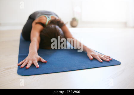 Woman doing stretching workout on fitness mat. Fit female performing yoga on exercise mat at gym. Child Pose, Balasana. - Stock Photo