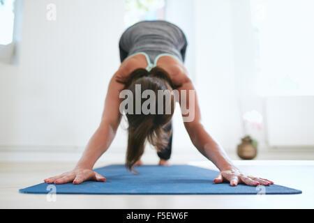 Portrait of woman practicing downward dog pose on yoga mat.  Fitness female in Adho Mukha Svanasana pose. - Stock Photo