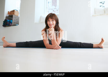 Photo of flexible woman doing the splits. Attractive female practices yoga at gym, looking at camera smiling. Upavistha - Stock Photo