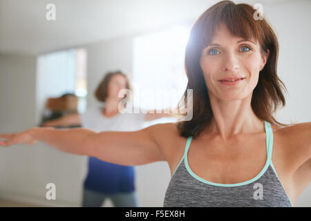 Two women doing stretching and yoga workout at gym. Female trainer with her student in background during physical - Stock Photo