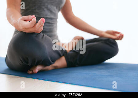 Close up of female sitting cross legged and hands on knees during meditation. Woman sitting in Lotus pose on exercise - Stock Photo