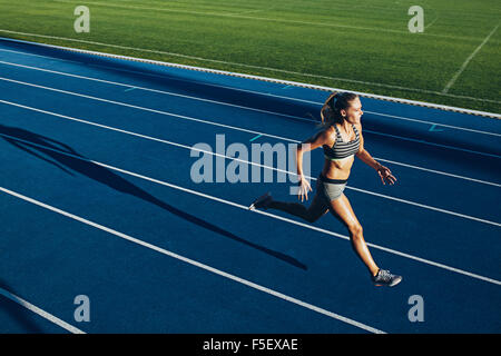 Young woman running on racetrack during training session. Female runner practicing on athletics race track. - Stock Photo