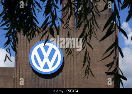 The VW-Logo on the facade of the Volkswagen factory behind a weeping tree. The photo was taken on 30 September 2015. - Stock Photo