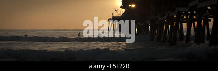 San Clemente, California, USA. 9th Dec, 2012. Three surfers share a sunset surf session in the water just south - Stock Photo