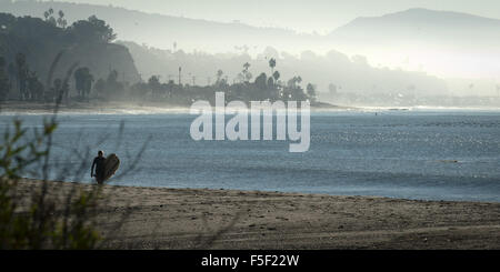 Dana Point, California, USA. 24th Nov, 2012. A young surfer makes her way up the beach to Boneyards at Doheny State - Stock Photo