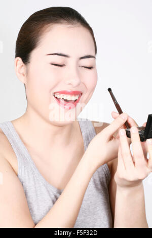 Woman laughing while she puts makeup on - Stock Photo