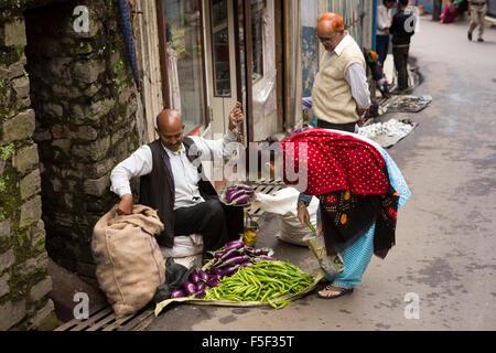 India, Himachal Pradesh, Shimla (Simla), Mall Road, man selling aubergines and large green chillies - Stock Photo