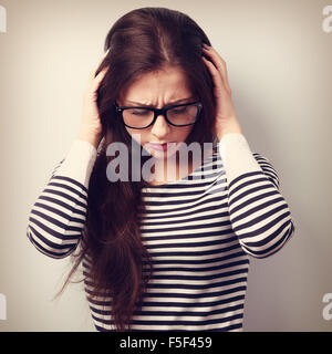 Business unhappy young woman with headache holding head the hands. Vintage portrait - Stock Photo