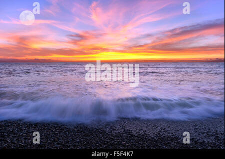 Ocean sunset moon is a color filled sky with the waves breaking on shore and the full moon rising in the background. - Stock Photo