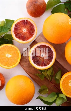 Mixed variety of navel and blood oranges on chopping board with leaves on rustic white wood table. - Stock Photo