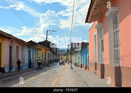 Colourful pastel houses lining a quiet residential street in Trinidad Cuba - Stock Photo