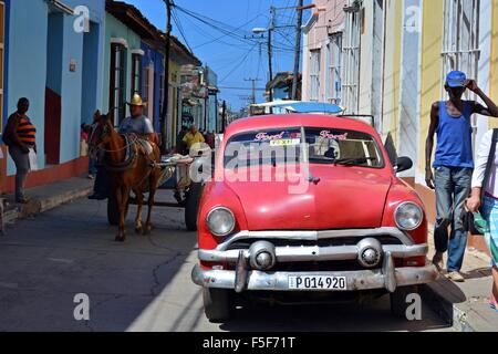 Old red Ford taxi parked in the sun on a colourful street in Trinidad Cuba with a horse and cart and locals walking - Stock Photo