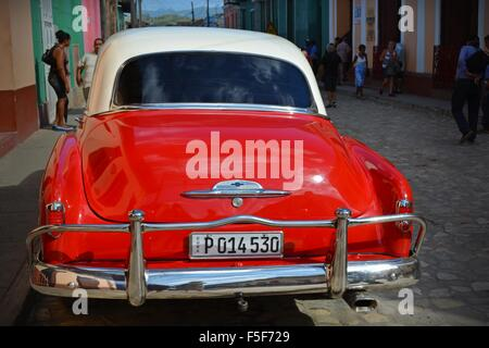 Vintage red and white car parked on a quiet street in Trinidad Cuba - Stock Photo