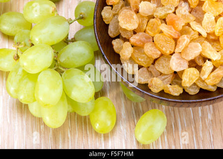 white seedless grapes and raisins sultanas  in a wooden bowl - Stock Photo