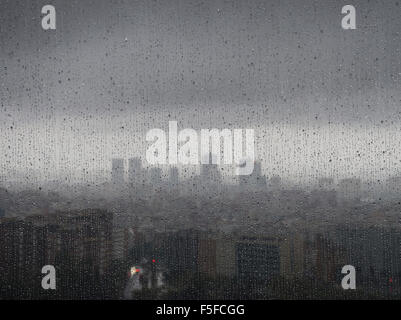 After heavy rainfall, the diffuse skyline of Barcelona is emerging in the twilight behind raindrops on a window. - Stock Photo
