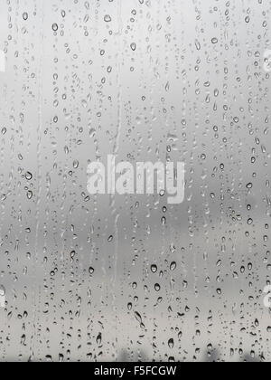 After heavy rainfall, many raindrops are trickling down a translucent glass window. Blurred, sad, grey sky in the - Stock Photo