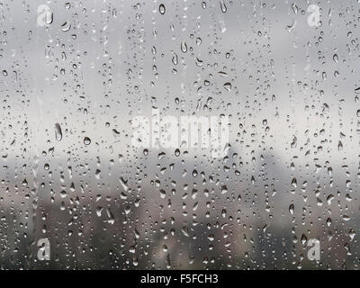 After heavy rainfall, many raindrops are trickling down a window. Diffuse silhouette of a city skyline emerges in - Stock Photo