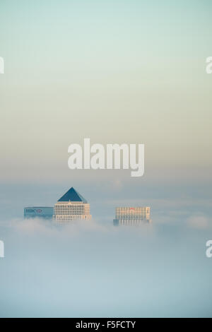 The roof tops of docklands high rise buildings protruding through the rising fog and clouds against a blue sky before - Stock Photo