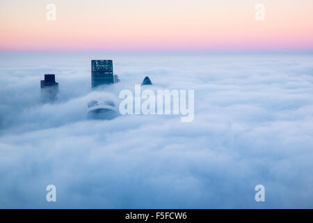 View from the Shard building London with the landscape covered in fog and cloud there are four buildings breaking - Stock Photo