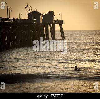 San Clemente, California, USA. 9th Dec, 2012. A lone young surfer in the waters just north of the San Clemente Pier - Stock Photo