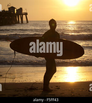 San Clemente, California, USA. 9th Dec, 2012. A surfer makes his way down the beach for a late afternoon sunset - Stock Photo