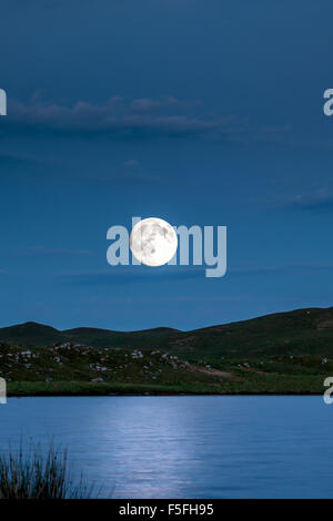 supermoon rising over a lake on the mountains - Stock Photo