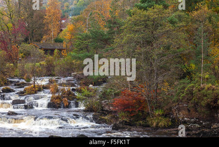 Part of the Falls of Dochart in the village of Killin in Perthshire, Scotland, with trees in autumn colours. - Stock Photo