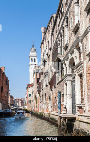 Side canal off  the Grand Canal, Venice, Italy, with classical, crumbling buildings, on a sunny day with blue sky - Stock Photo