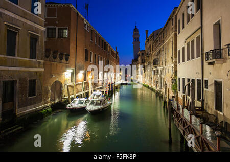 Venetian sightseeing by night: typical illuminated side canal off the Grand Canal with classic buildings and moored - Stock Photo