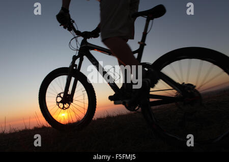 Laguna Beach, California, USA. 06th May, 2012. MTB rider TIM LANE in silhouette at sunset rides the trails in Aliso - Stock Photo