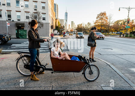 New York, NY - Mother and children in a bakfiet, or Dutch Utility Bike, wait on the sidewalk to cross the West Side - Stock Photo