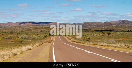 Panoramic view of highway slicing through vast outback landscape towards barren hills of Flinders Ranges rising - Stock Photo