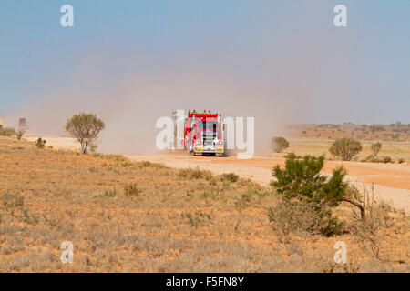 Road train, huge red semi-trailer / truck loaded with mining machinery ahead of cloud of dust on Australian outback - Stock Photo