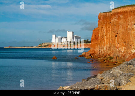 Huge white grain silos at Port Giles, on red coastal cliffs beside ocean, rising into blue sky over Yorke Peninsula - Stock Photo