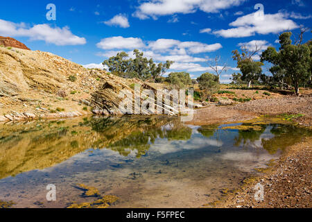 Crystal clear pool of water of Chambers River with blue sky reflected in mirror surface at Mount Chambers gorge - Stock Photo