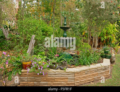 Decorative garden feature with low stone wall, ornate fountain, plants in containers, hemmed by lawn, flowers, shrubs, - Stock Photo
