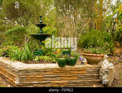 Decorative garden feature with low stone wall, ornate fountain Stock ...
