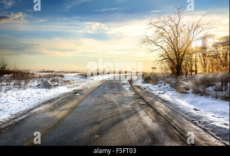 Road in winter at the beautiful sunset - Stock Photo