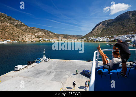 People on the deck of a ferry during a stop-over in the port of Kamares in Sifnos island, Greece - Stock Photo