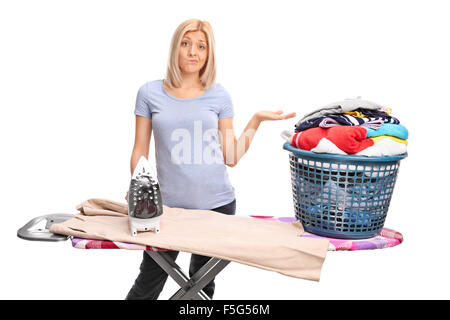 Displeased young woman posing behind an ironing board and gesturing with her hand isolated on white background - Stock Photo