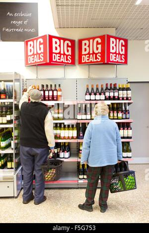 Old man and woman pensioners shopping in a supermarket in the wine aisle. - Stock Photo